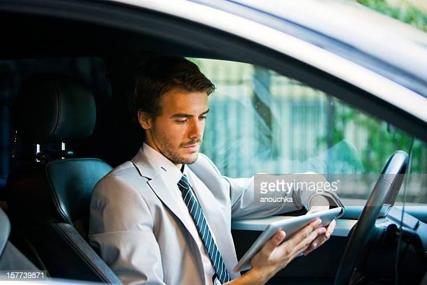 Hübscher junger Geschäftsmann mit Tablet PC im Auto
