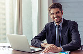 Portrait of handsome young businessman in formal suit using a laptop, looking at camera and smiling while working in office