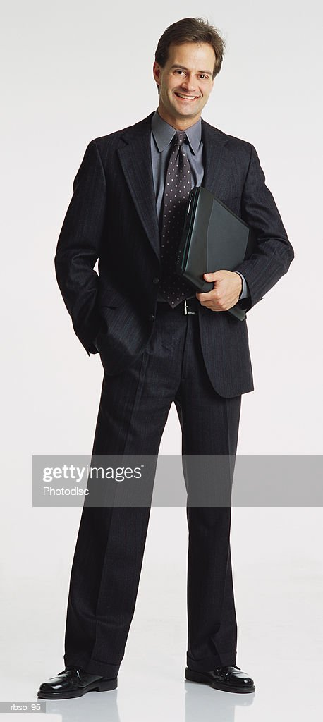 handsome young caucasian businessman in a dark suit facing the camera tucking a laptop under his arm : Stock Photo