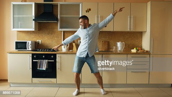 Handsome young funny man dancing in kitchen at home in the morning and have fun on holidays : Foto de stock