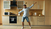 Handsome young funny man dancing in kitchen at home in the morning and have fun on vacation