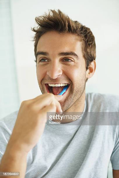 Handsome young guy brushing his teeth