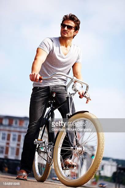 Beau jeune homme debout avec le vélo
