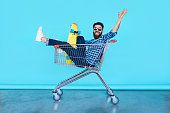 handsome young hipster man sitting in the shopping cart while holding a skateboard over blue turquoise color background
