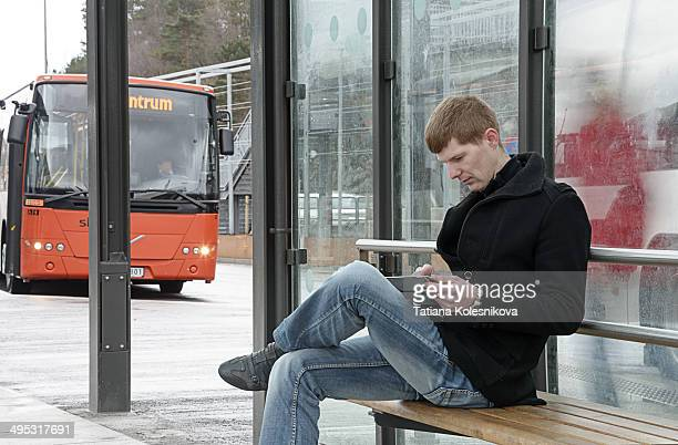 Handsome young man awaits commuter bus