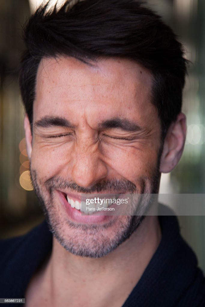 Handsome, young man bursting into laughter