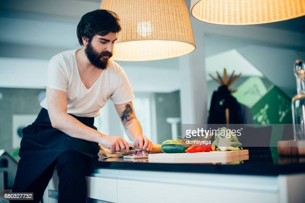 Handsome young man cutting onion and reading recipe to prepare food on digital tablet