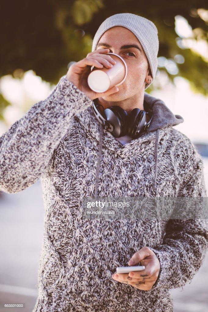Knappe jongeman drinken koffie en het bedrijf van een slimme telefoon : Stockfoto