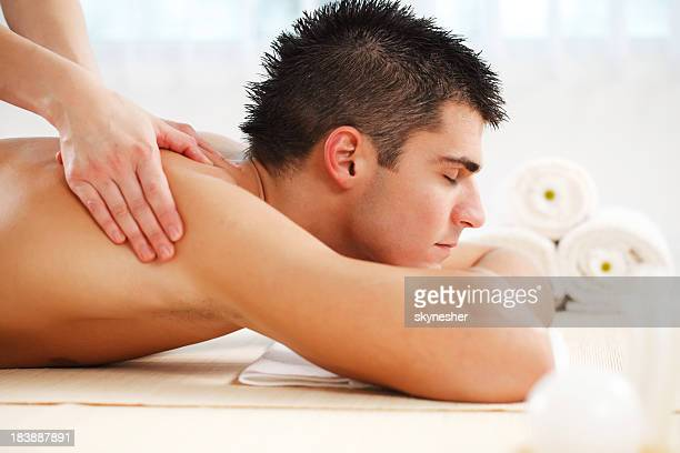 Handsome young man getting a massage at the spa centre.