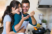 Shot of handsome young man giving his wife to try the food he is preparing in the kitchen at home.