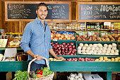 Handsome young man holding basket at vegetable stall in supermarket