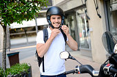 handsome young man in a modern city adjusting motorcycle helmet in summer