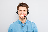 handsome young man in work in  call-centre with headphones and smiling