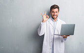 Handsome young man over grey grunge wall wearing white coat using laptop doing ok sign with fingers, excellent symbol