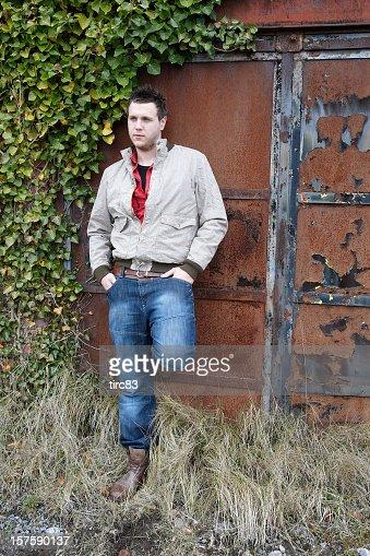 Handsome young man portrait alongside rusted door