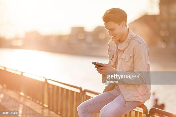 Beau jeune homme envoi de messages sur téléphone mobile à l'extérieur