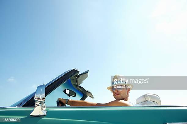 Beau jeune homme assis dans une voiture décapotable-copyspace