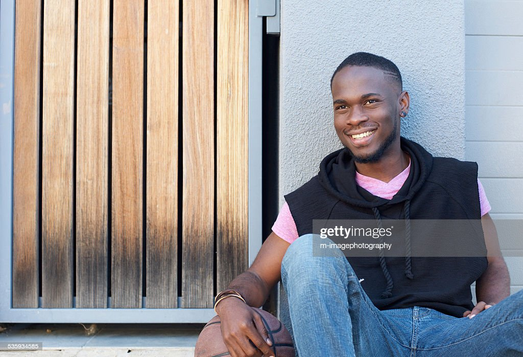 Handsome young man sitting outdoors with basketball : Stock Photo