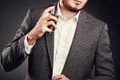 Handsome Young Man using Perfume. Young Man in Business Suit. Casual Style