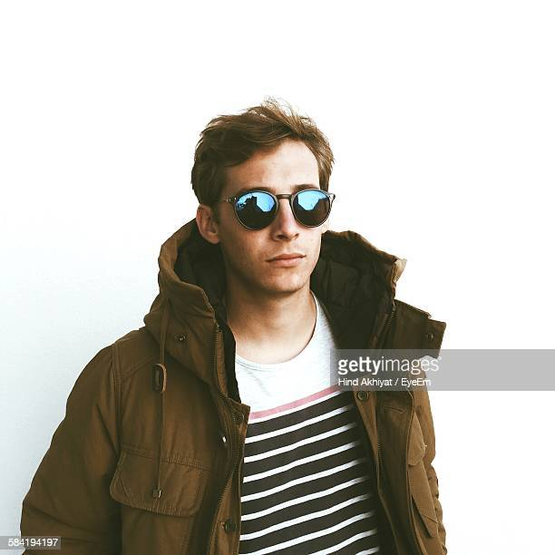 Handsome Young Man Wearing Sunglasses And Jacket Standing Against White Background