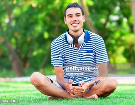 Bel giovane uomo con le cuffie in erba verde : Foto stock