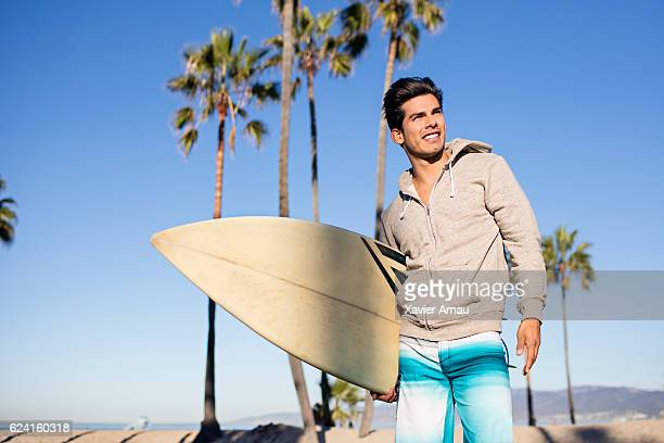 Handsome young man with surfboard on the beach