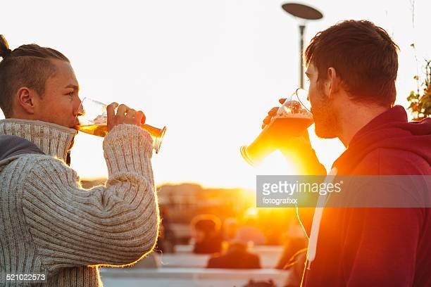 handsome young men drinking beer in front of backlit