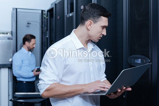 Handsome young technician looking at the control panel : Stock Photo