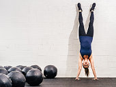 Photo of a young fit woman doing a handstand exercise at a gym.