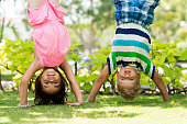 Two playful children standing on their hands in the park
