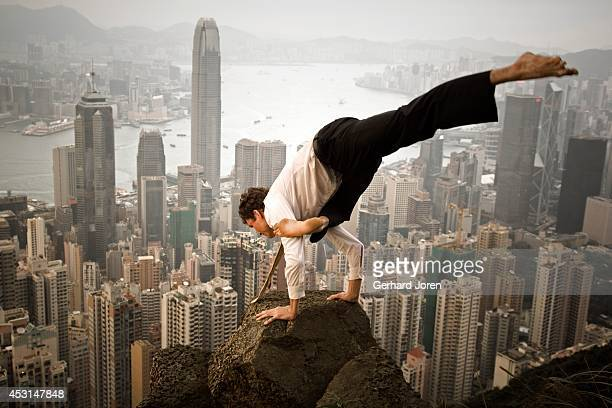A handstand yoga pose on a cliff above the city MODEL RELEASED
