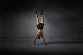 handstanding for athletic man, dark background