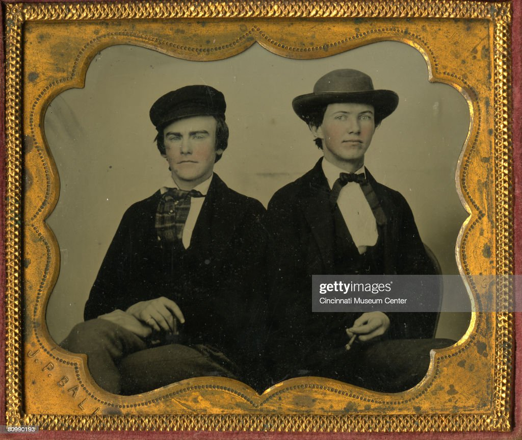 Handtinted giltcased ambrotype portrait of two unidentified men as they sit next to one another each with a cigar in his hand late 1850s or early...