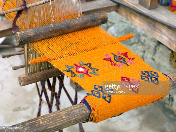 A handwoven woollen yathra skarf on a Tibetan style loom outside her farmhouse in the Tang Valley Bumthang Central Bhutan Yathra is a hand woven...