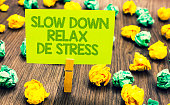 Handwriting text Slow Down Relax De Stress. Concept meaning Have a break reduce stress levels rest calm Paperclip retain written words yellow paper paper lobs laid on wooden floor