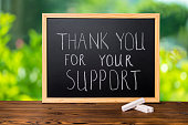 handwriting text thank you for your support is written in chalkboard on green light background and rustic wooden board, close up
