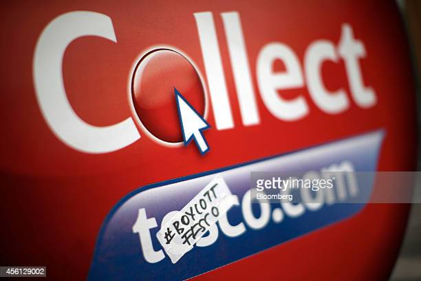 A handwritten '#Boycott Tesco' sticker sits on a sign advertising Tesco Plc's clickandcollect service outside one of the company's supermarket stores...