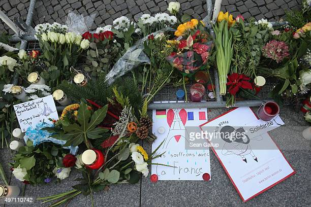 A handwritten sign in French reads 'We suffer with France' among flowers and candles left by mourners at the gate of the French Embassy following the...
