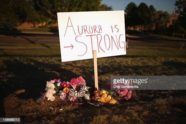 Handwritten signs are posted at a makeshift memorial across the street from the Century 16 movie theater the day after a gunman killed 12 people and...