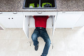 horizontal image of a man in a red top and jeans lying under the kitchen sink cabinet and fixing a leak