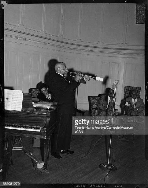 WC Handy playing trumpet on stage with woman and two men seated on armchairs in background Pittsburgh Pennsylvania September 1952