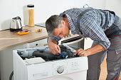 Full length of handyman checking washing machine with flashlight in kitchen