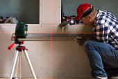 Handyman drawing a line on dry wall with help of laser leveler