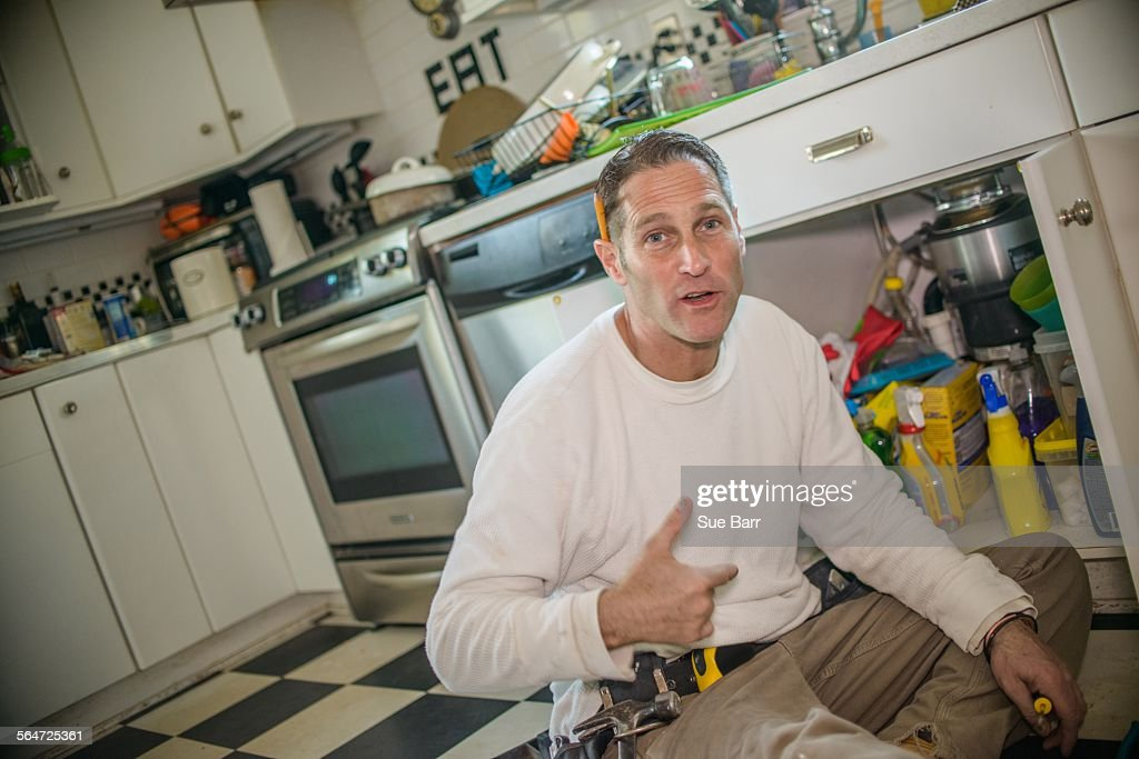 Handyman fixing kitchen sink pipe : Stock Photo