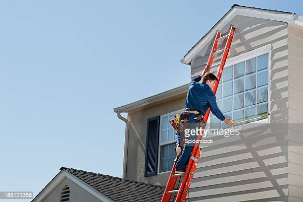Handyman In Uniform Measuring Window
