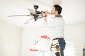 Attractive young handyman stepping on a ladder and fixing a ceiling fan