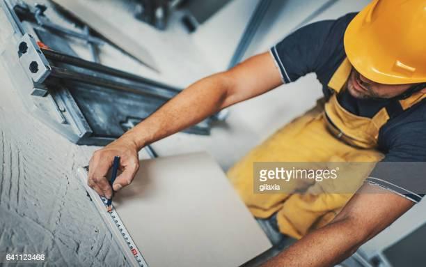 Handyman laying ceramic tiles.