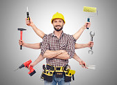 Cheerful carpenter looking at camera with tolls in six hands
