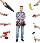Cheerful carpenter looking at camera with tools all around, white background