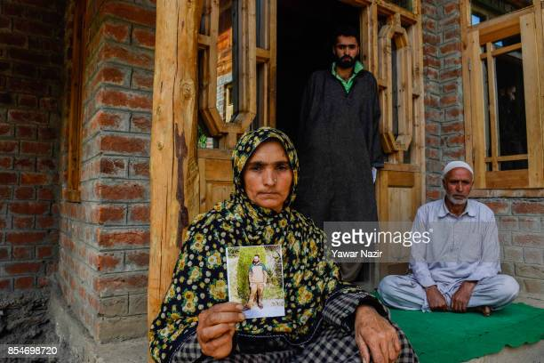 Haneefa Begum holds a picture of her missing son Manzoor Ahmad who has been missing since August 31 after he and his neighbour Nasrullah Khan were...